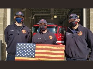 three firefighters holding wooden flag